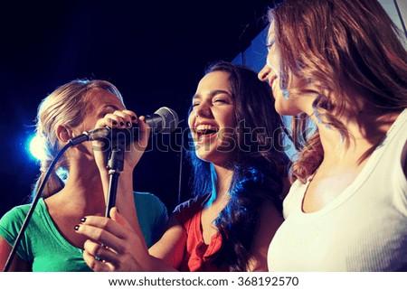 happy young women singing karaoke in night club - stock photo