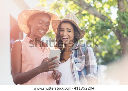 Happy young women using mobile phone - stock photo