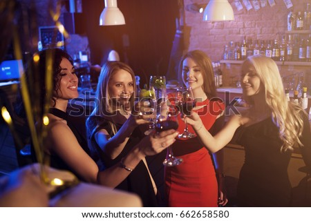 Happy young women with glasses of wine and cocktails enjoying a night out in stylish bar.