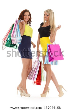 Happy young women with shopping bags on a white background. - stock photo