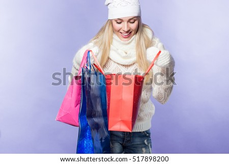 Happy young women with shopping bags. Young woman bought Christmas presents. Young woman in a hat and mittens. Winter.