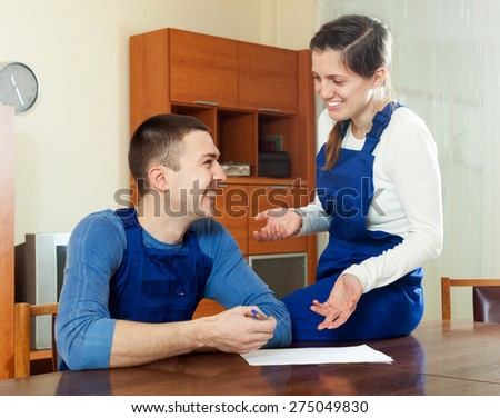 happy young  workers in uniform reading financial documents  at table  in the room