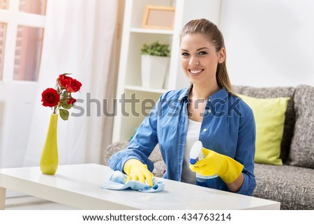 Happy young worth woman cleaning the table - stock photo