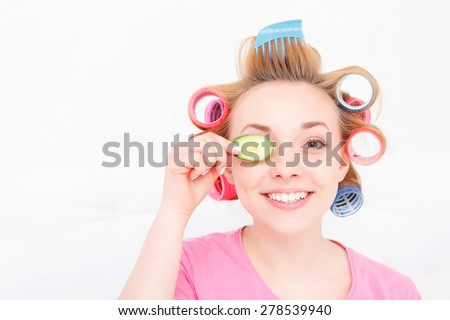 Happy youth. Young pretty girl wearing colorful hair curlers and pink T-short holding a slice of cucumber near her eye and smiling isolated on white background - stock photo