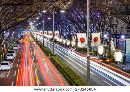 Harajuku, Tokyo, Japan traffic flows below Japanese flags at night.  - stock photo