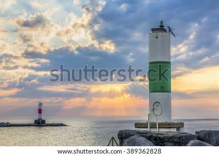 Harbor beacons on breakwaters are backed by a glorious morning sky over Lake Michigan at Kenosha, Wisconsin. - stock photo
