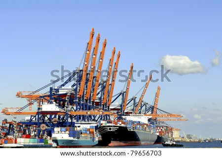 Harbor cranes  and container ship in harbor of rotterdam - stock photo