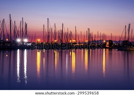 Harbor in the evening, silhouettes of luxury sailboat moored in the port, beautiful view on yachts with many glowing lights, active summer vacation - stock photo