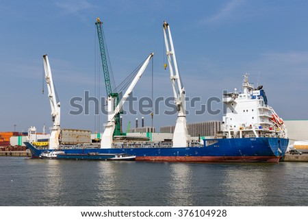 Harbor of Antwerp with cargo ships moored at quay with big cranes, Belgium - stock photo