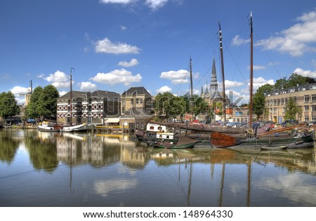 Harbor of Gouda, Holland with historical houses and boats - stock photo