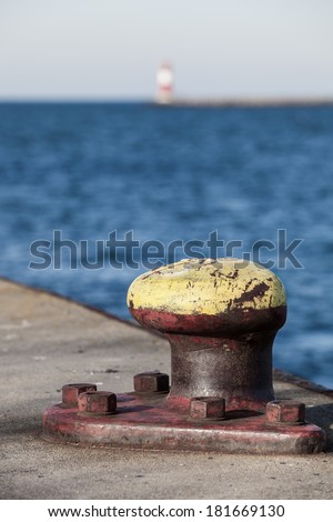 Harbor pier with bollard and blue sea with a lighthouse at the background/Pier Bollard - stock photo