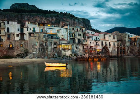 harbor view of old houses in Cefalu at dusk, Sicily - stock photo