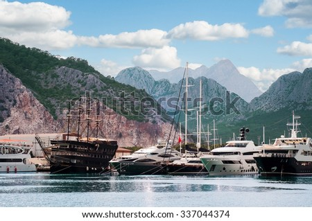 Harbor with anchored ships, sail boats, yachts in bay among mountains in Mediterranean sea