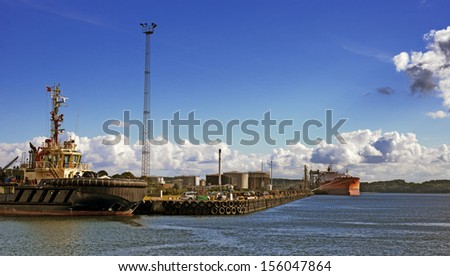 Harbor with tanker and tugboat  - stock photo