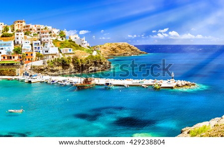 Harbour with marine vessels, boats and lighthouse. View from cliff on Bay with beach and architecture Bali - vacation destination resort, with clear turquoise ocean waters, Rethymno, Crete, Greece - stock photo