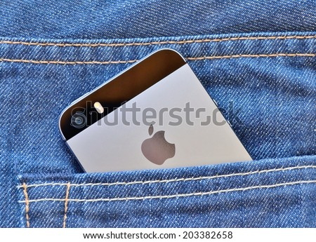 HARD, AUSTRIA - MARCH 22, 2014 Apple iPhone 5s, space gray, in a jeans pocket. - stock photo