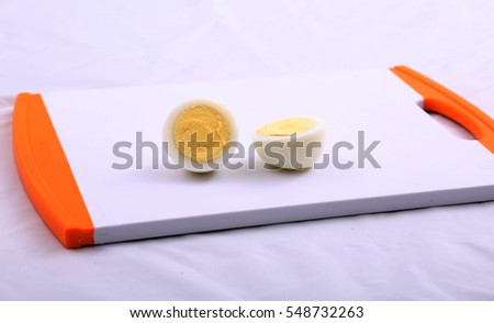 Hard Boiled Egg on a white and orange plastic cutting board.