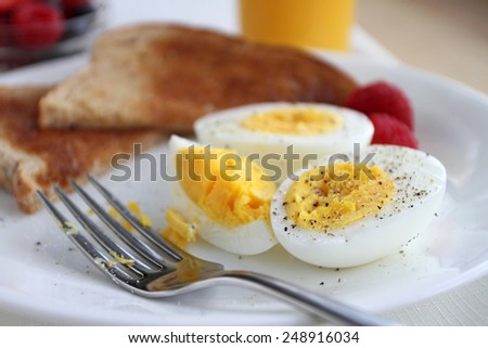 Hard boiled eggs for breakfast with toast, orange juice, fruit, salt, and pepper. - stock photo