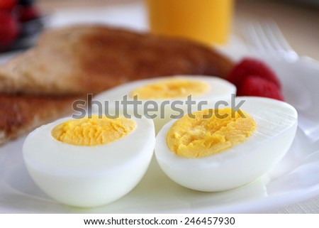 Hard boiled eggs, toast, fruit, and orange juice for breakfast. - stock photo
