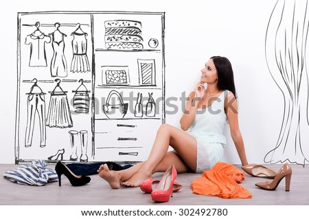 Hard choice. Thoughtful young woman in dress looking at the sketch on the wall while sitting on the floor with clothes and shoes laying around her  - stock photo