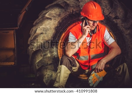 Hard Construction Business Concept with Caucasian Businessman Making Business Call While Seating Inside Heavy Duty Bulldozer Tire. - stock photo