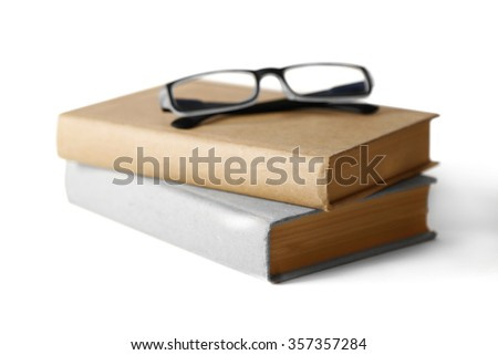 Hard covered books and eyeglasses on it isolated on white background - stock photo