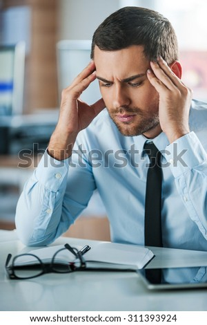 Hard day in office. Frustrated businessman touching his head while sitting at his working place - stock photo