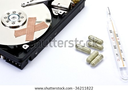 Hard disk with patch applied, along with some medical tools - stock photo