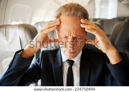 Hard flight. Frustrated mature businessman touching his head with hands and keeping eyes closed while sitting at his seat in airplane  - stock photo