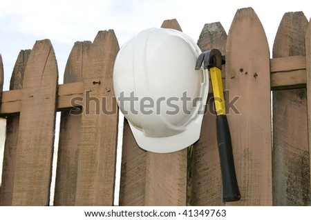 Hard Hat and Hammer hanging on a weathered fence - stock photo