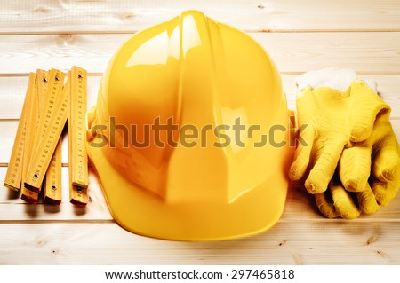 Hard hat, ruler and protection gloves on wooden background. Construction concept  - stock photo