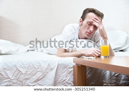 hard morning. man with a headache try ti wake up. Glass of apple juice and pills are on the table.  - stock photo