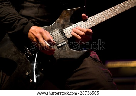 Hard Rock male Heavy Metal Guitarist playing black electric guitar in live music gig concert