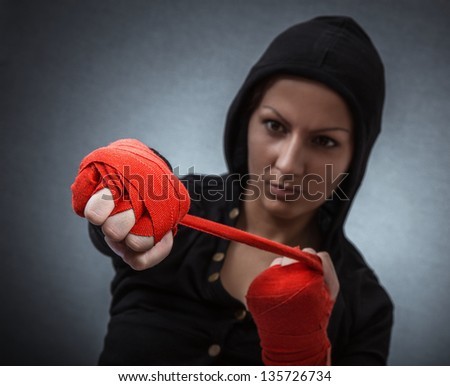 Hard sport woman ready for fight. Fighter girl with hoodie over dark gray background