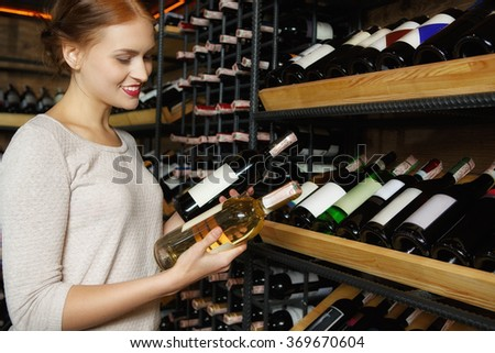 Hard to choose! Portrait of an attractive female choosing between two bottles of wine in her hands standing in a wine store cellar - stock photo