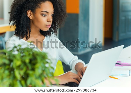 Hard work ensures success. Concentrated young African women working on laptop while sitting at working place  - stock photo