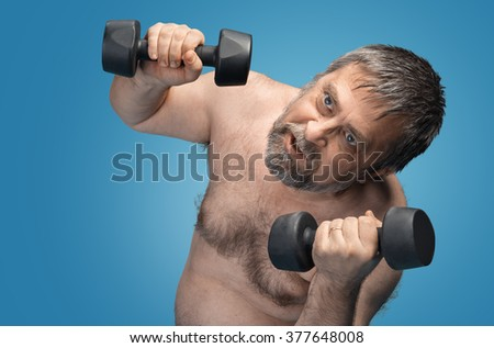 Hard work for a healthy lifestyle concept. The man does sports exercises isolated on blue background with copyspace