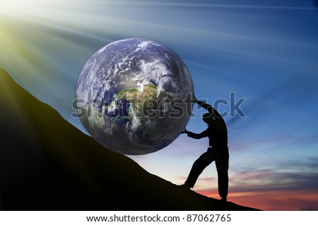 hard work.The person rolls the globe on mountain. - stock photo