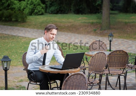 Hard working businessman. Attractive young tired man in formal shirt and tie working on laptop while sitting at the table outdoors - stock photo