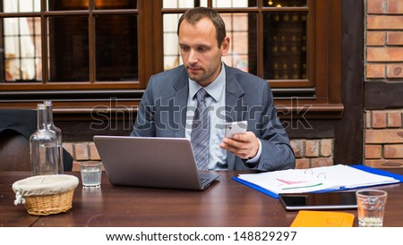 Hard working businessman in restaurant with laptop and mobile phone. Close-up.