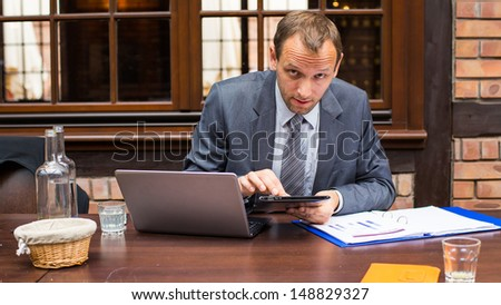 Hard working businessman in restaurant with laptop and pad.