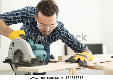 Hard working carpenter cutting wooden plank   - stock photo
