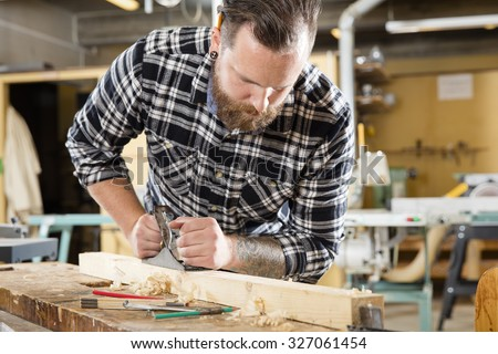 Hard working craftsman working with planer in a workshop for woodwork. Handsome man with tattoo and beard. - stock photo