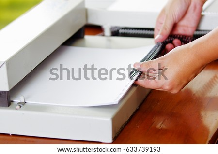 Hard working man using a white useful Binding machine