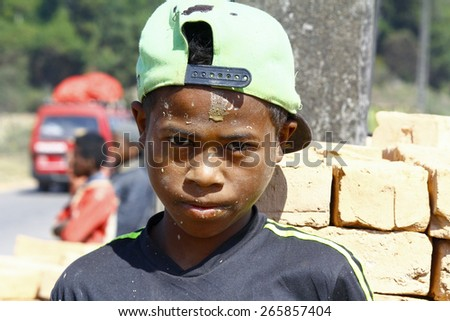 Hard working poor malagasy boy with dirty face - poverty in Madagascar - stock photo