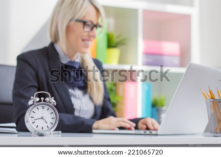 Hard working woman is always on time at work - stock photo