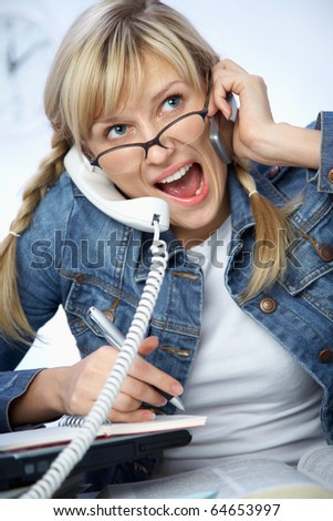 Hard-working young blonde crying to phone - stock photo