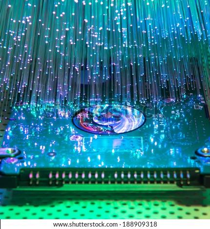 harddisk with fiber optical background - stock photo