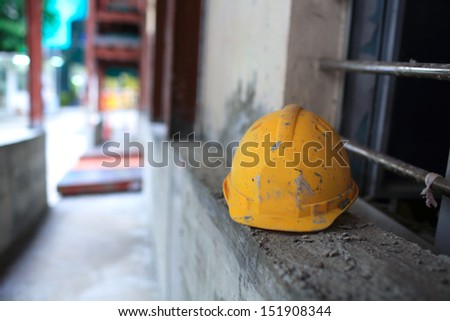 hardhat or yellow safety hard helmet have been put down with the chinese construction site background  - stock photo