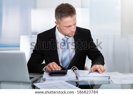 Hardworking businessman analyzing a report sitting at his desk using a calculator and reading a report in a binder - stock photo